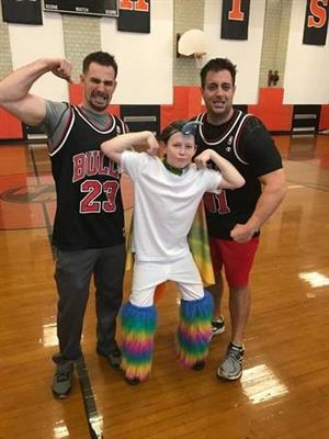 two gym teachers posing with a student
